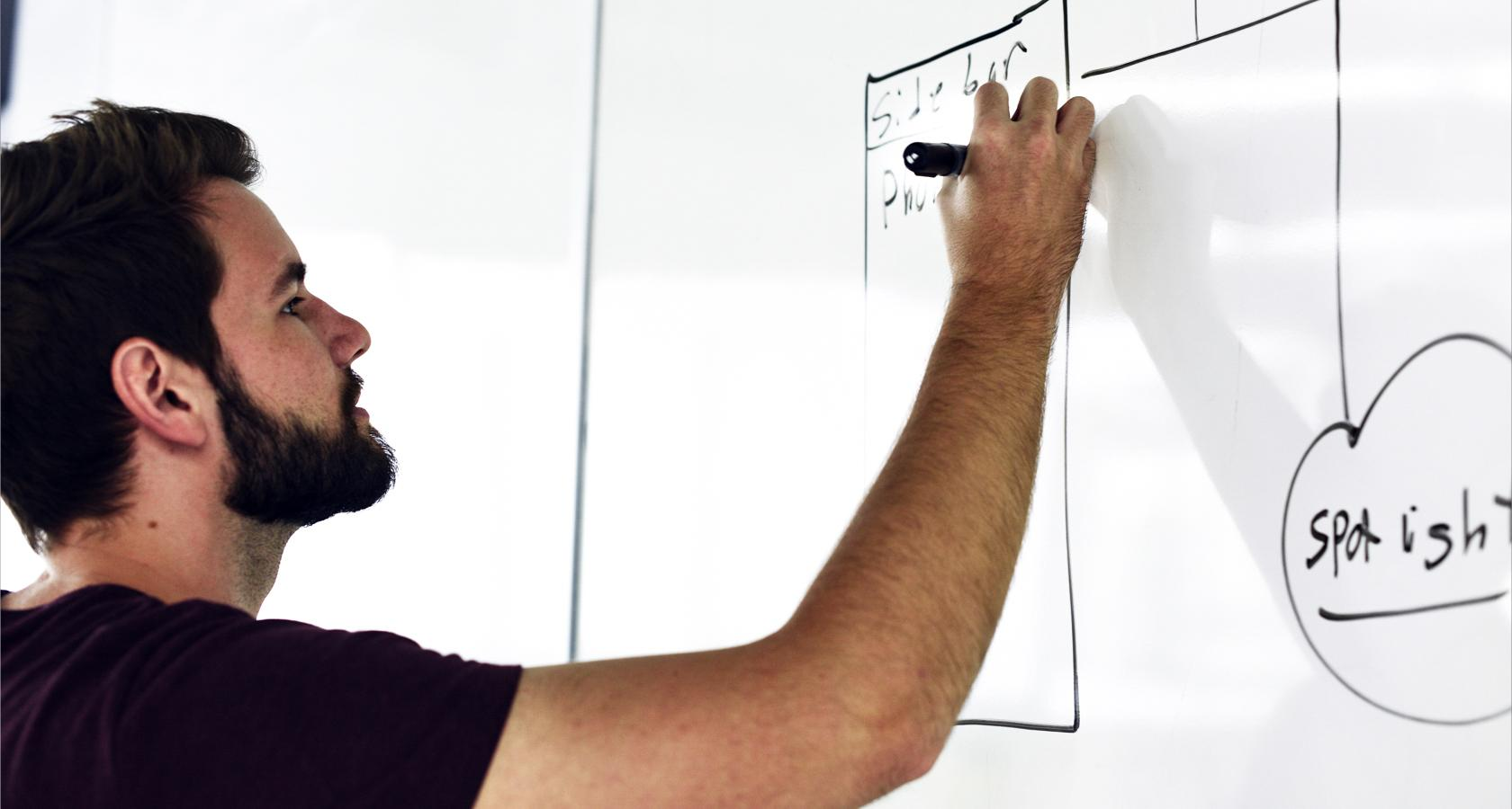 Web designer drawing information architecture on whiteboard