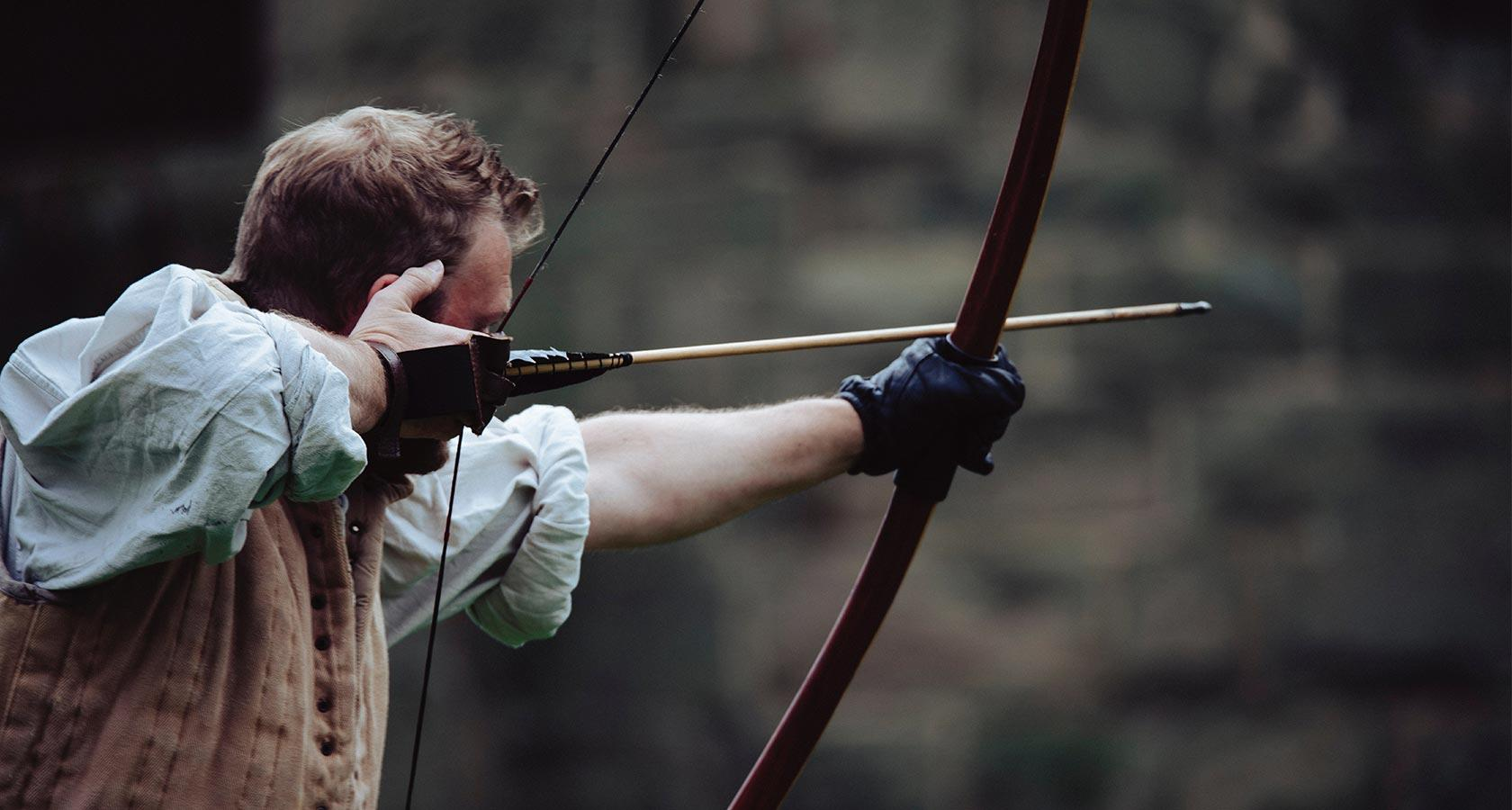 Man holding a bow aiming for a specific target