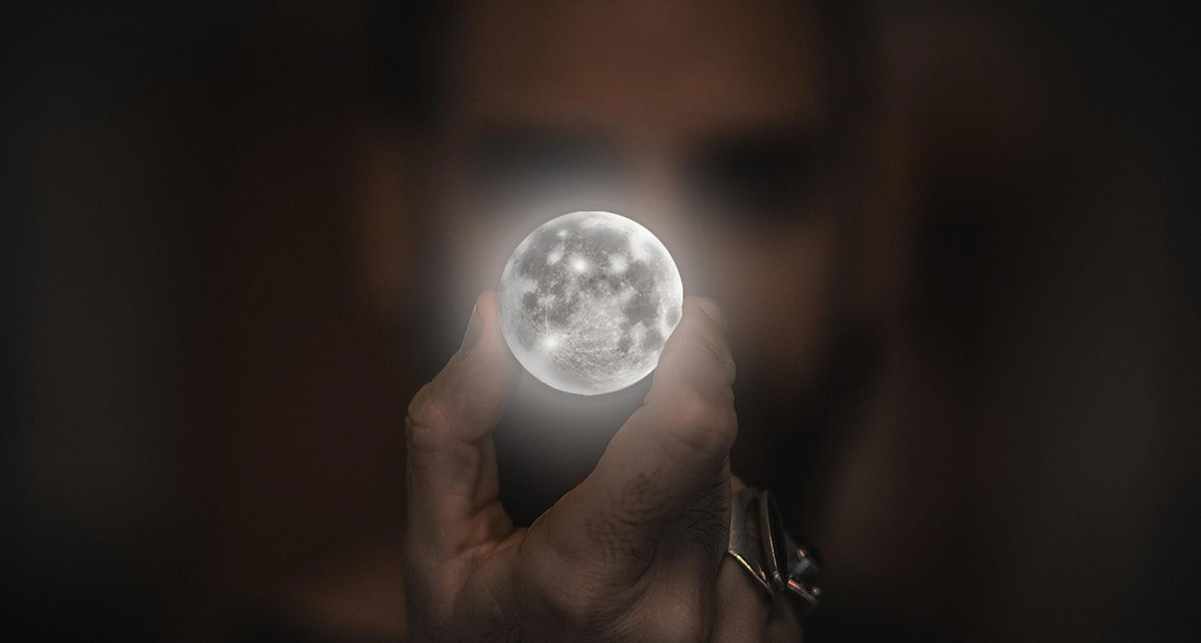Man holding a non-realistic moon