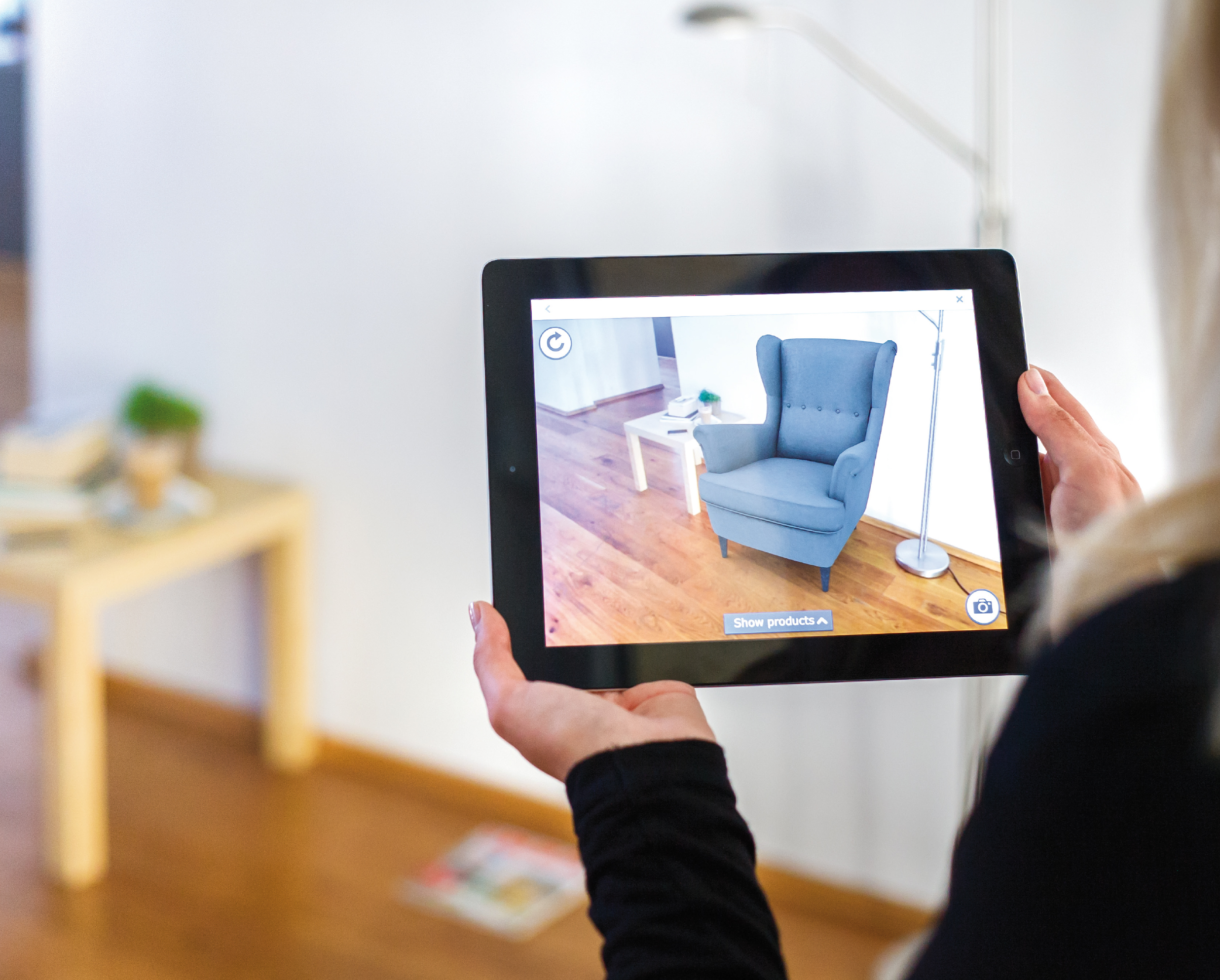 A superimposition-based AR app showing an armchair in its view of a room. In the background behind the tablet, one can see that there is no armchair in that spot