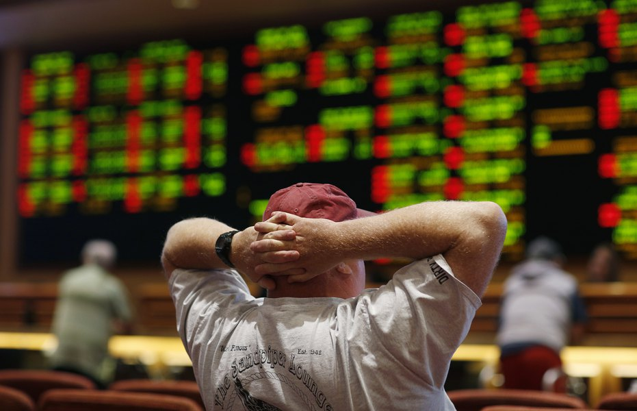 Photo of a man watching a sports betting board.