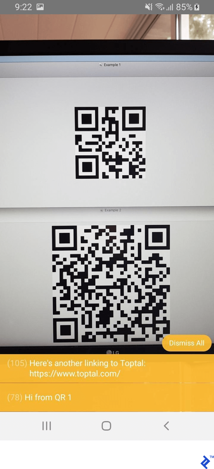 "The same camera angle as before, now with console popups at the bottom having decoded the messages in the QR codes: ""Hi from QR1"" and Toptal's web site address."